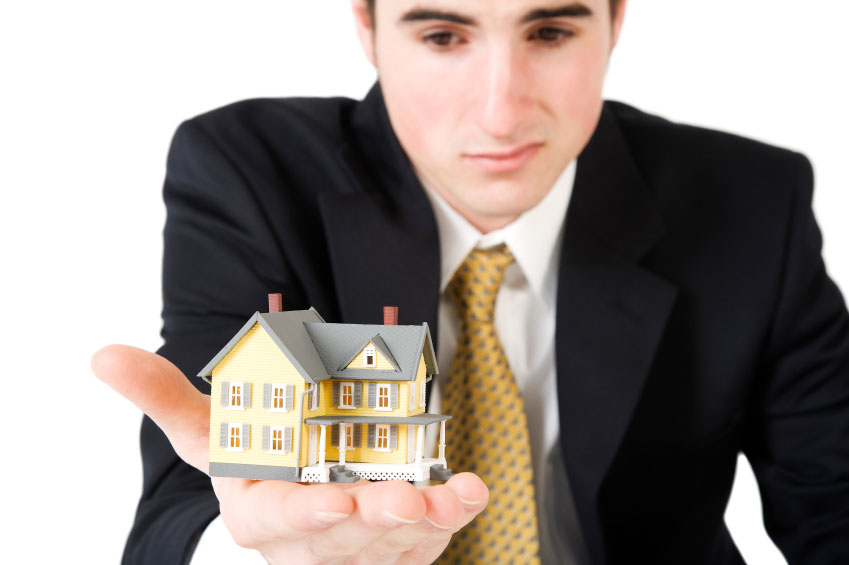 Landlord holding up a small model home in the palm of his hand